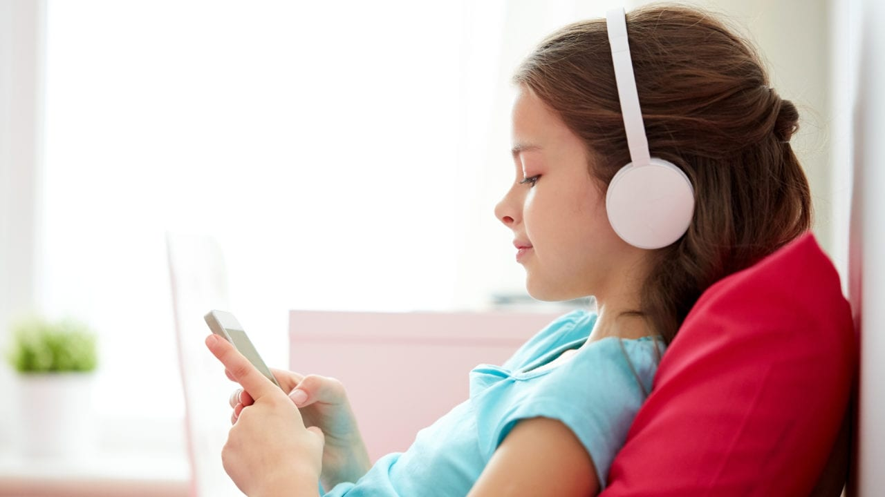 girl listening with headphones in her home