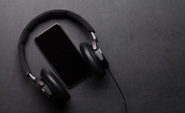 Black Headphones and smartphone on leather desk table