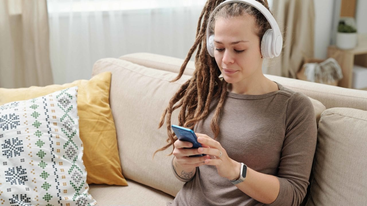 Young woman with dreadlocks sitting on sofa listening to her phone wiearing white headphones