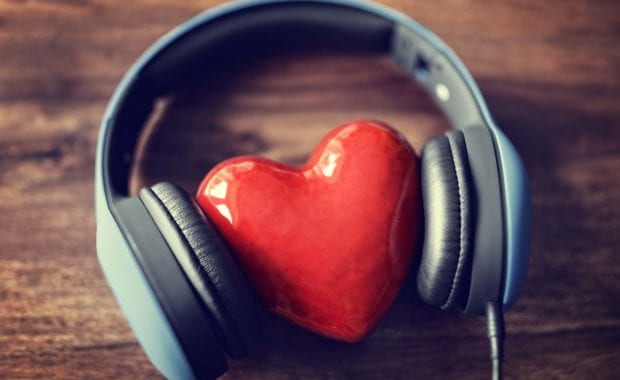 Headphones laying on a wooden table with a heart nestled in between
