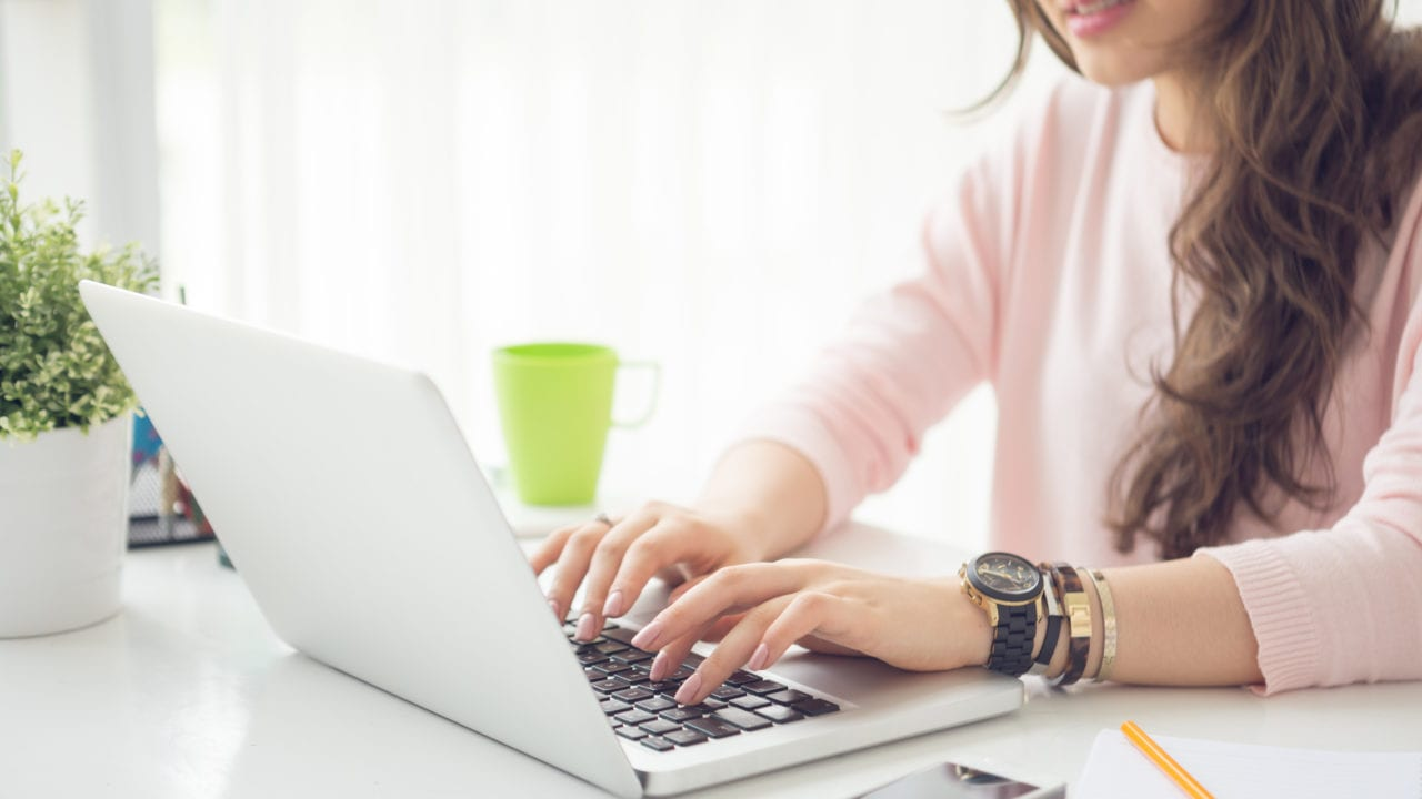 Cropped image of female working on laptop