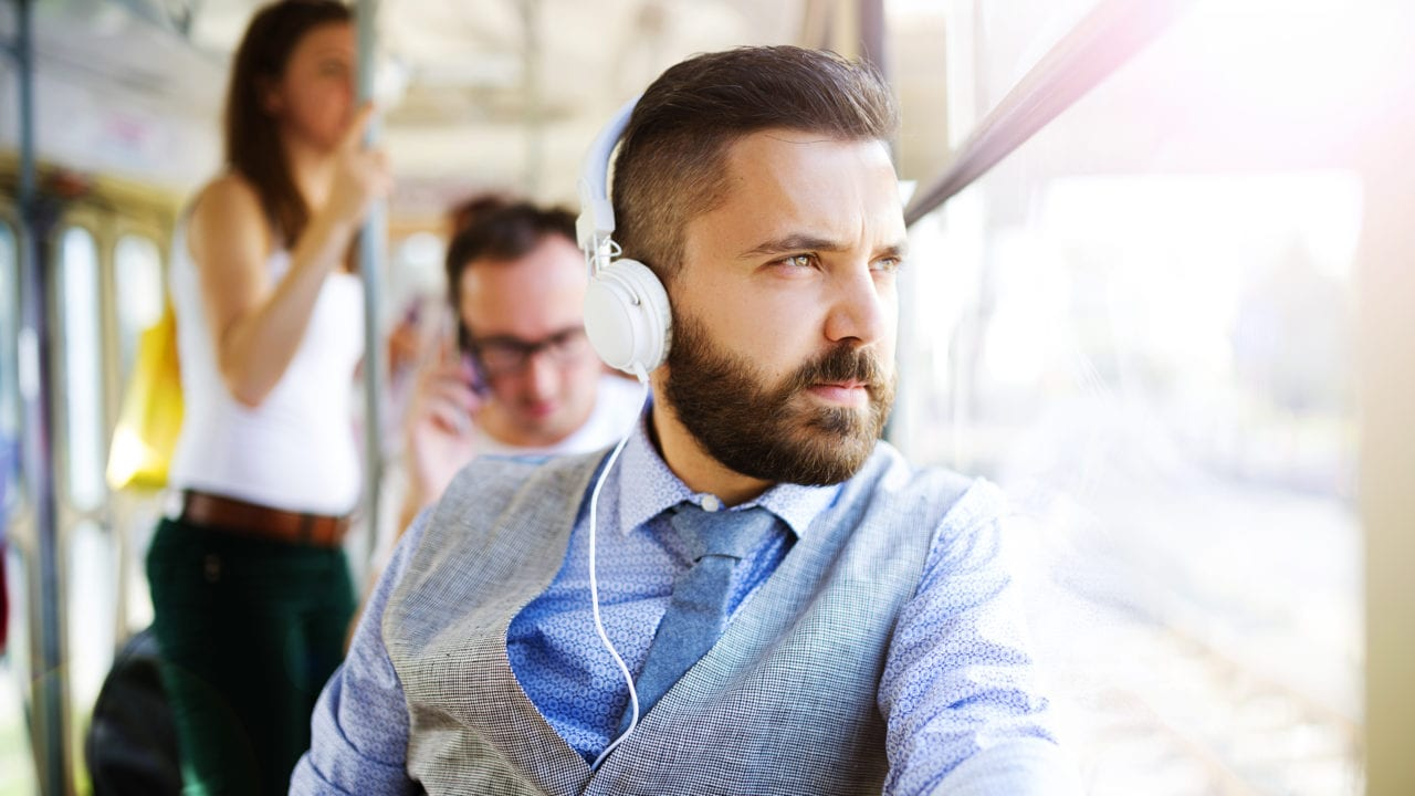 Handsome modern man with headphones traveling by tram in town