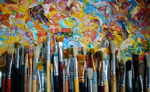 op view of rows of paintbrushes laying on abstract colorful oil paint artwork.
