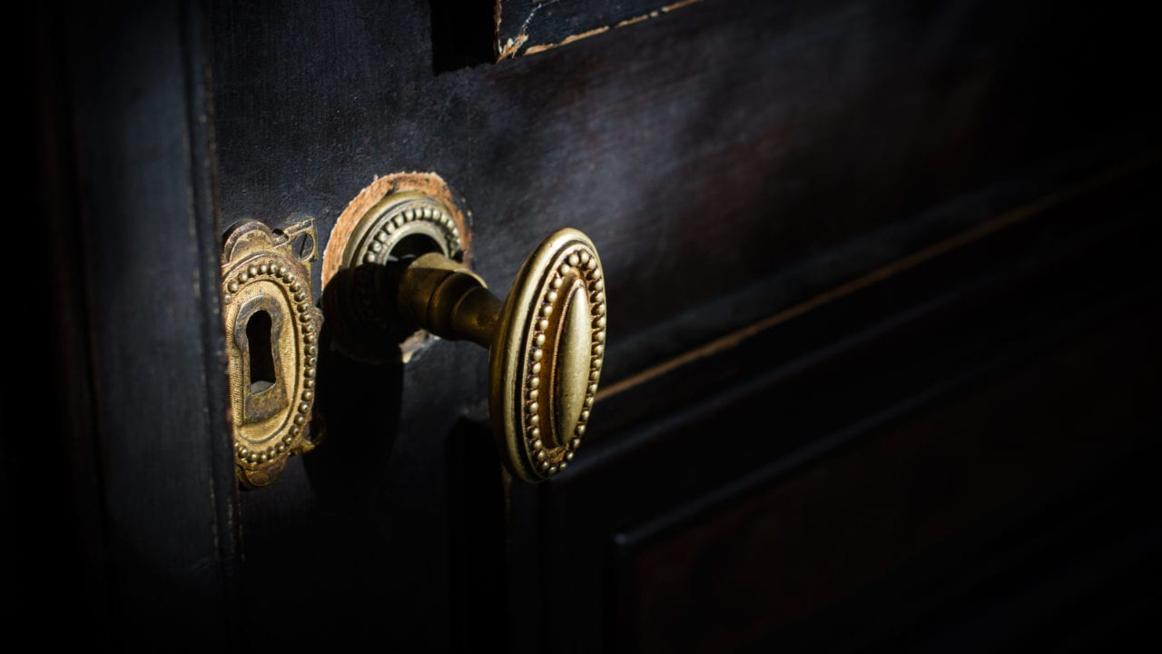 Side view detail of vintage antique brass door knob with metallic carvings and keyhole on black wooden door.