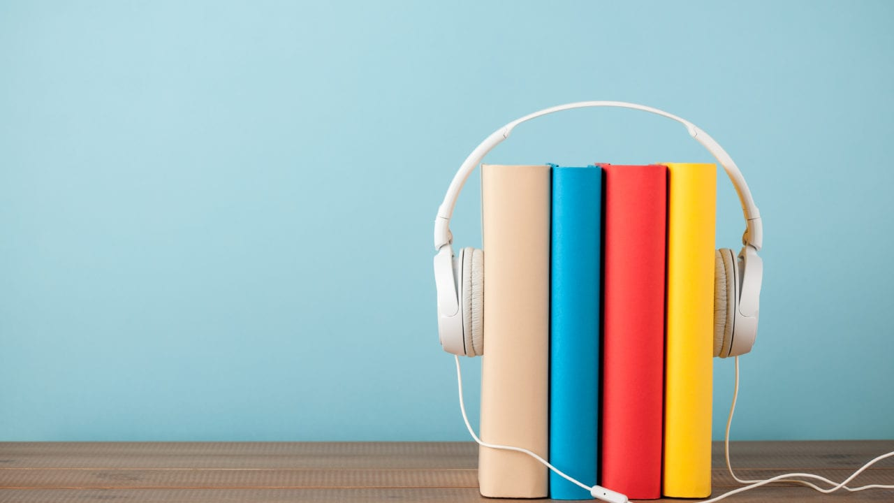 Books with multicolored bindings on a wooden table with headphones around them