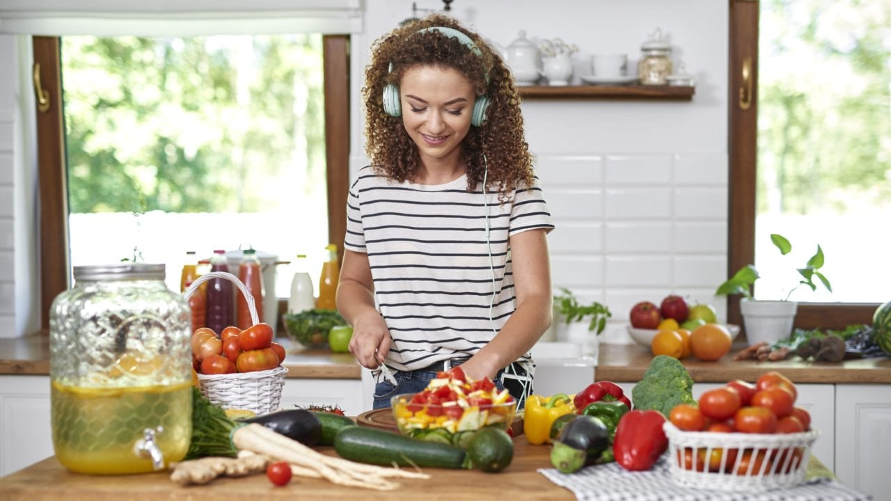 Young woman in kitchen cutting produce to cook while listening to headphones