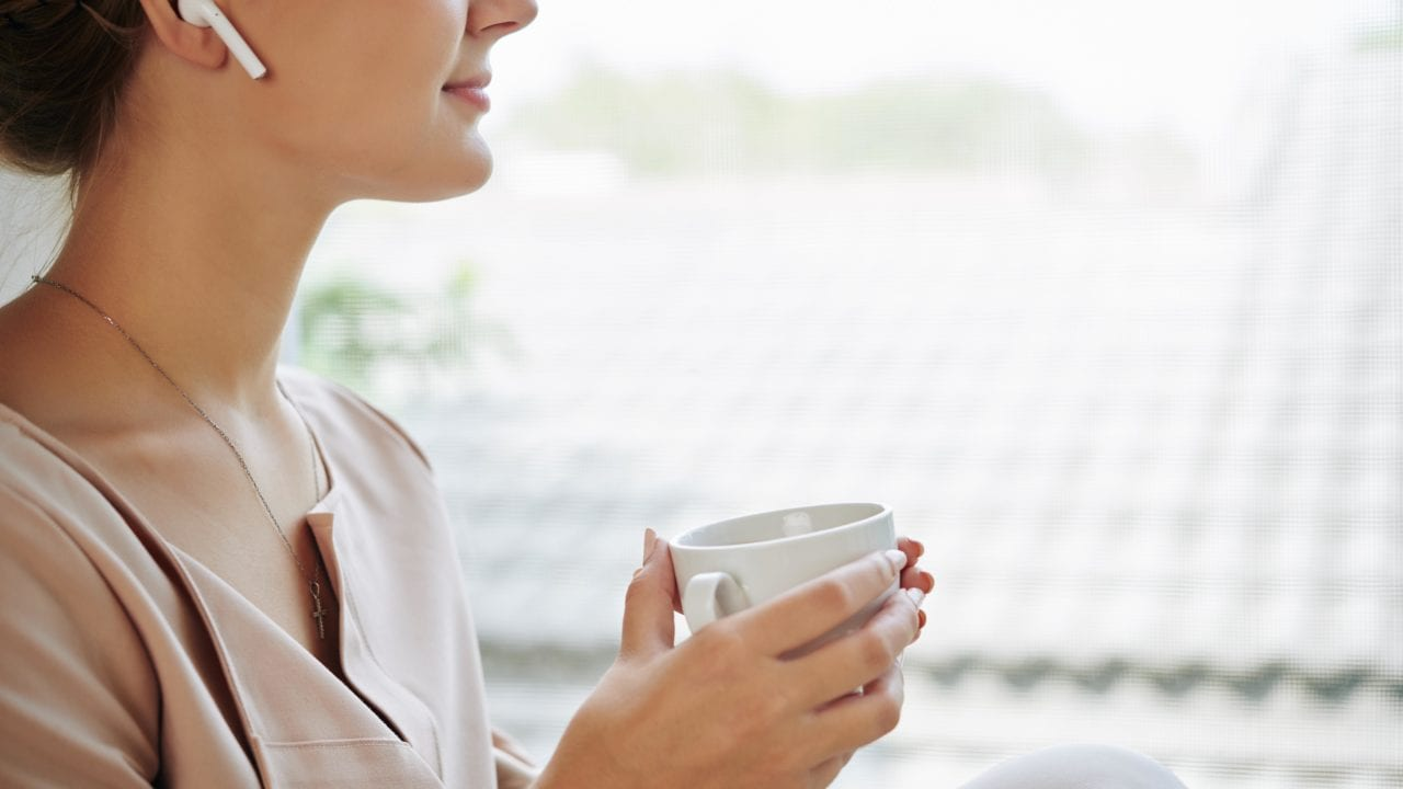 Beautiful smiling young woman wearing earbuds when listening to podcast, drinking tea and looking through window