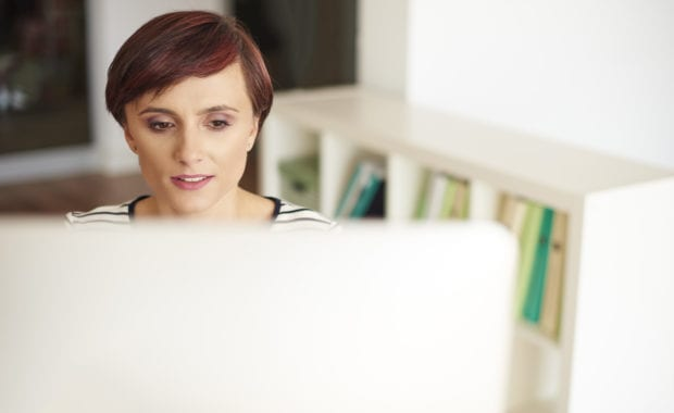 Woman with short auburn hair looking at computer screen in home office with shelves behind her.
