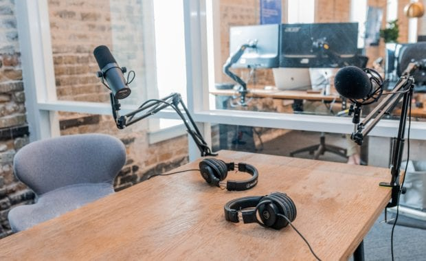 Open studio with glass walls, long wooden table with two sets of microphones and headphones