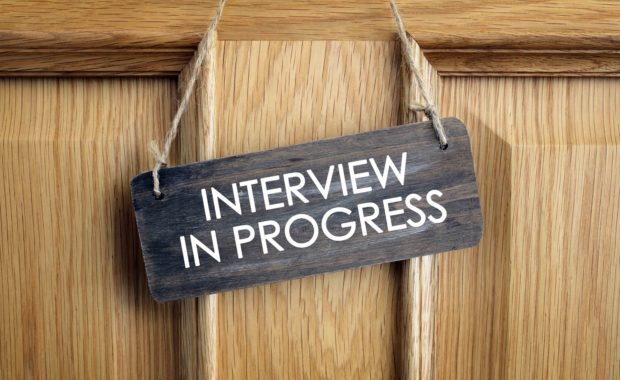 Light wooden door with a small slate sign stating interview in progress hung on it.