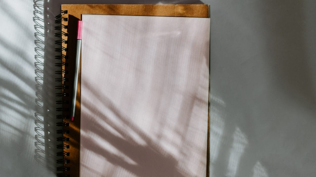 Notebook with pen and paper on a white surface with shadow cast from plants