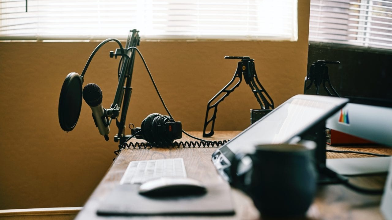 Close up, side view of desk with computer and microphone set up and a cup of coffee lit with a large window with blinds