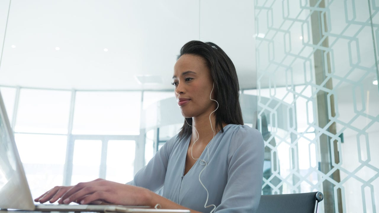 Female executive listening earbuds while using laptop at desk in a brightly lit office from windows and a glass wall behind.