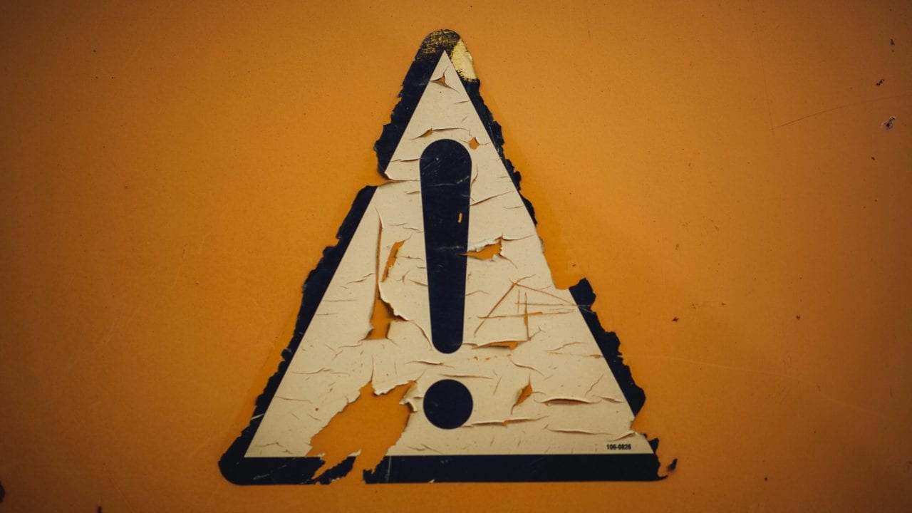 Worn looking triangle decal with exclamation point inside against orange background.