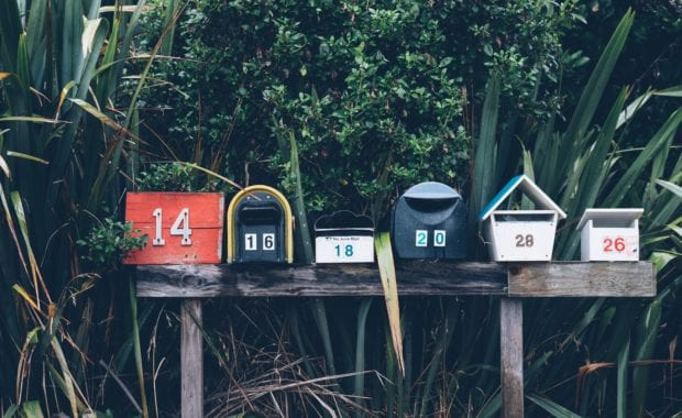 Line of differently shaped mailboxes with woods behind.