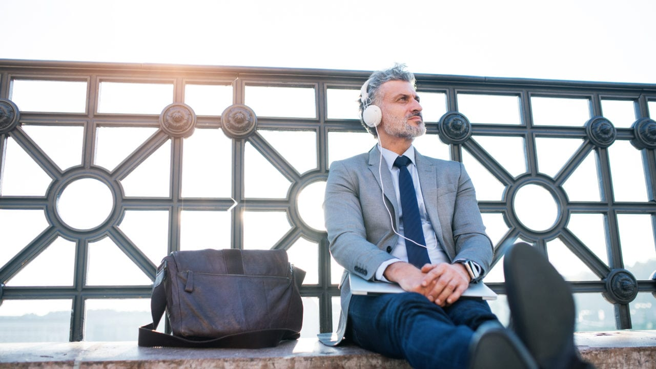 Handsome mature businessman sitting on a bridge, holding laptop and using headphones.