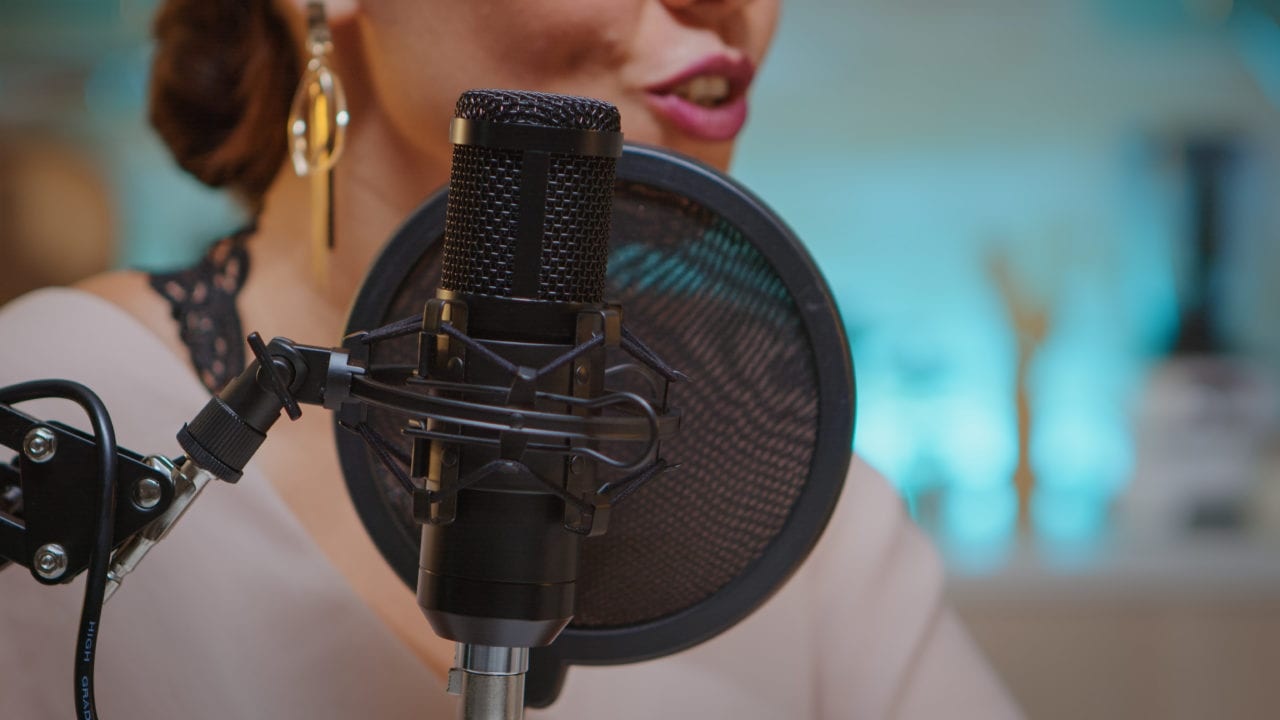 Presenter recording voice in home studio for media using professional microphone.