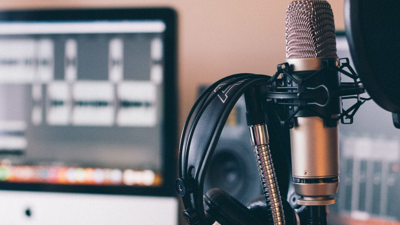 Close up of microphone and headphones with computer with editing software in the background.