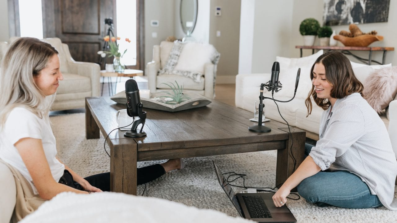 Two women sitting on the floor opposite each other, each with microphones and one looking at a laptop