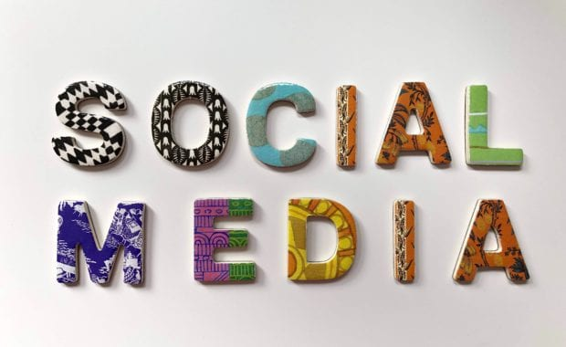 The words social media spelled out using multicolor designed letter magnets